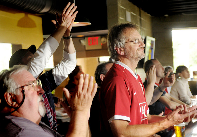 Alan Pugsley, in red for Manchester United, reacts as the U.S. team scores a goal in the World Cup game between the U.S. and Pugsley's native England on Saturday. He and other soccer fans watched from G.R. DiMillo's restaurant on Preble Street in Portland.