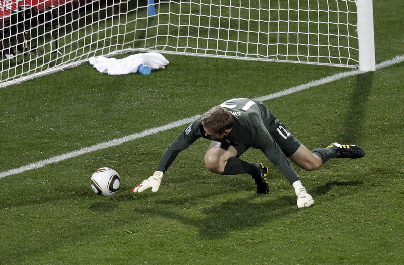England goalkeeper Robert Green scrambles for the ball after initially stopping American Clint Dempsey's bouncing 25-yard shot. The ball rolled into the net for a 1-1 tie.