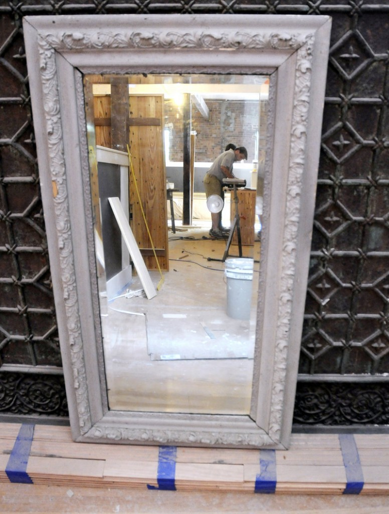 Tom Munroe is reflected in an old mirror as he finishes tables for Havana South, a new restaurant on Wharf Street in Portland. The restaurant is filled with antiques collected by owner Michael Boland, such as this mirror that came from a house on Danforth Street.