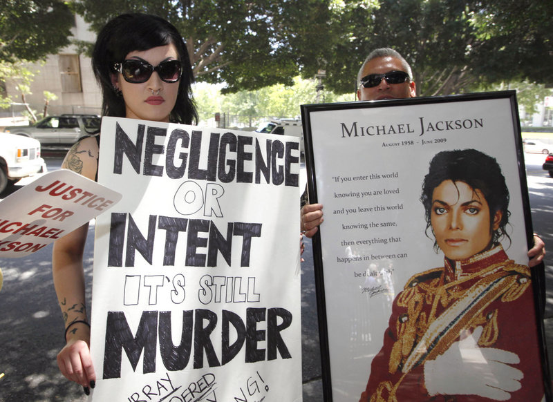 Sheila Baragas holds a poster critical of Dr. Conrad Murray outside a Los Angeles courthouse Monday. A judge said he doesn't have the authority to revoke the accused doctor's license.