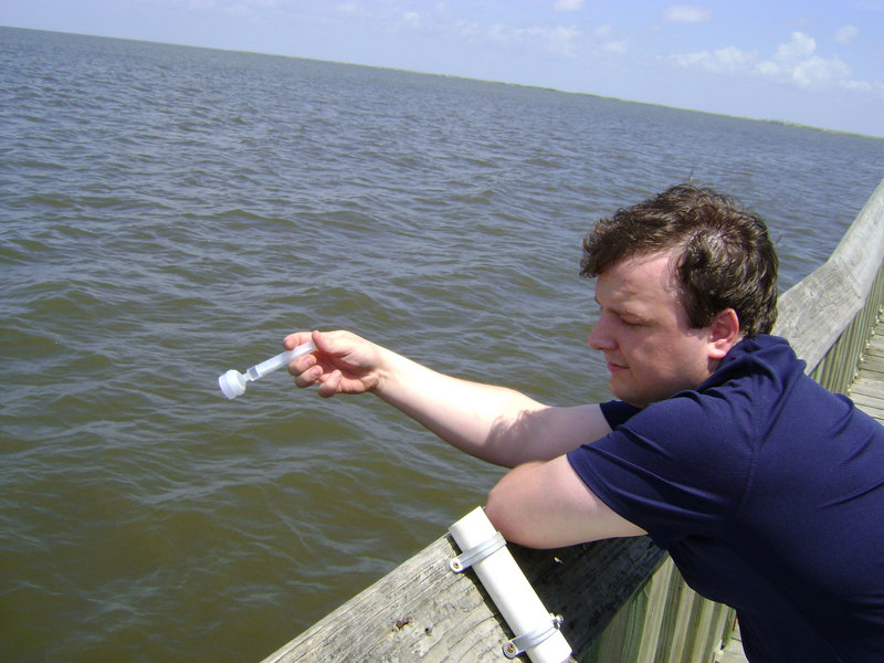 Tom Schwarz of Orono takes a sample of Gulf water from a pier in Cypremort Point State Park in Louisiana. The sample is part of environmental testing.