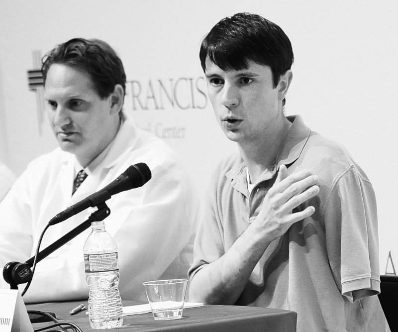 Jonathan Metz, who tried to amputate his left arm to free himself from his furnace boiler, speaks at a news conference Tuesday about his ordeal. At left is Dr. Scott Ellner.