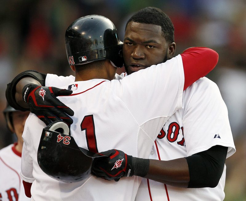 David Ortiz of the Red Sox receives a hug from Victor Martinez after hitting a two-run homer in the first inning of the 6-3 victory against the Diamondbacks.