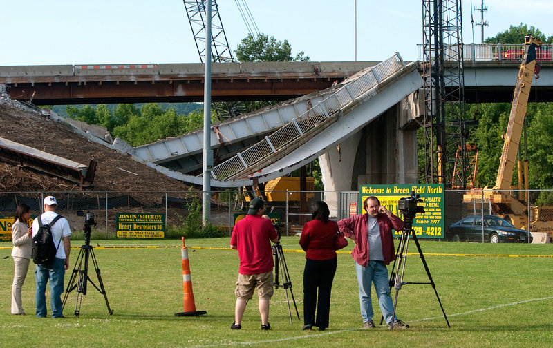 Journalists set up cameras in front of a bridge section that collapsed on Route 63 in Naugatuck, Conn., on Tuesday. One worker, an excavator operator, was critically injured.