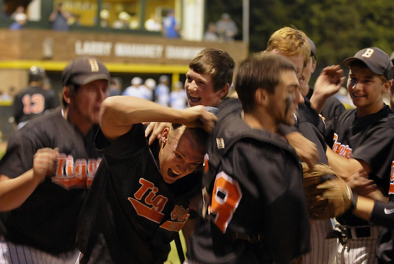 With the Western Class A title in sight, the Biddeford players mob Tyler Parker, second left, after his eighth-inning run gave the Tigers a 4-2 lead against Westbrook on Tuesday.