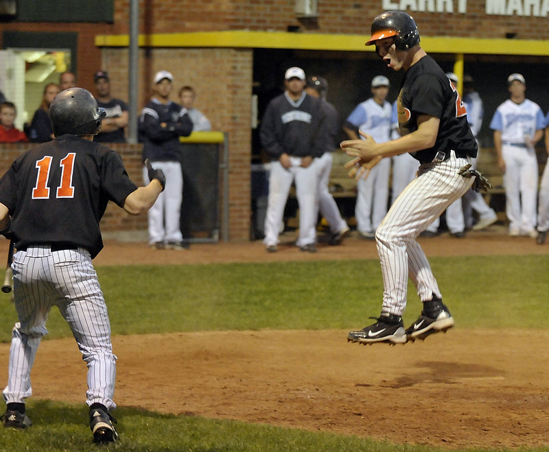 Tyler Audie gives Biddeford the lead in the eighth inning Tuesday night, scoring on a passed ball as teammate Travis Vigneault welcomes him home. The Tigers scored a second run in the inning and went on to defeat Westbrook 4-2 and capture the Western Class A championship.
