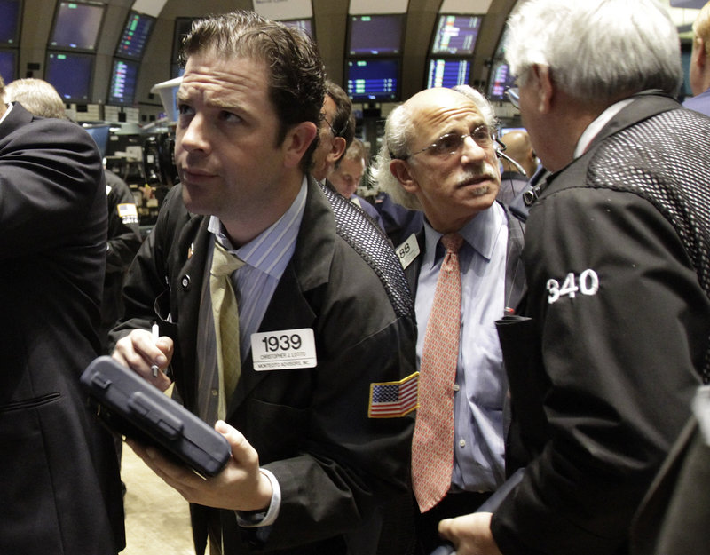 Trader Christopher Lotito checks prices from the floor of the New York Stock Exchange Wednesday. BP actions helped the market recover from an early drop on housing news.