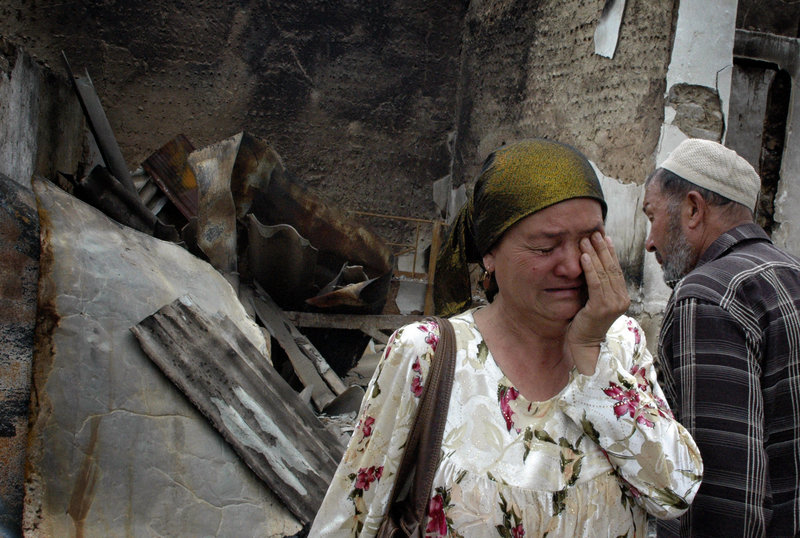 An ethnic Uzbek woman and her husband see that their home has been burned Thursday in Jalal-Abad, Kyrgyzstan, amid the ethnic violence that has killed more than 200 people.