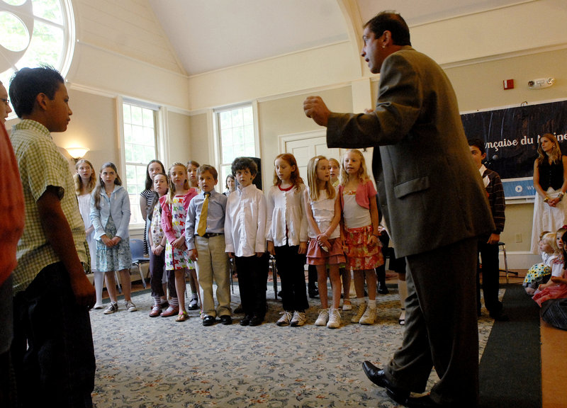 Didier Carribou, a teacher, leads the children in a French song during their end of the year ceremonies held at the South Freeport Church, across the street from the school.