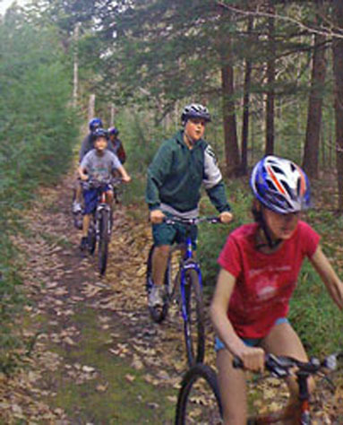 Bonny Eagle Middle School students Katherine Utz, Chris Smith and Will Myrick ride the two miles of cross country trails behind the bus garage at the Buxton school. The trails were created to take advantage of bicycles and other equipment the school has. Physical education teacher Todd Drinkwater is hoping the school can get more equipment for the students to use.