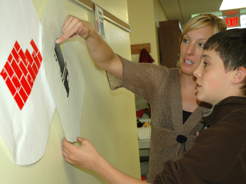 Thornton Academy art teacher Amy Goodness chats with eighth-grade student Curtis Huard about the prints he made from a lino block. The blocks designed by Huard and his classmates were used to print a