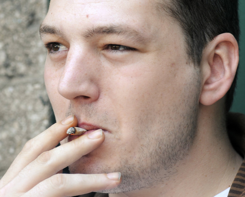 Joe Richards, 27, smokes a cigarette he rolled outside the YMCA on Forest Avenue in Portland. Richards says he started smoking on his 16th birthday after feeling pressure from friends.