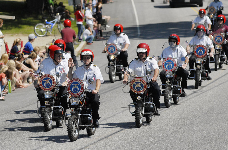 Members of the Kora Cycle Corps rumble in formation on their mini-bikes down the parade route.