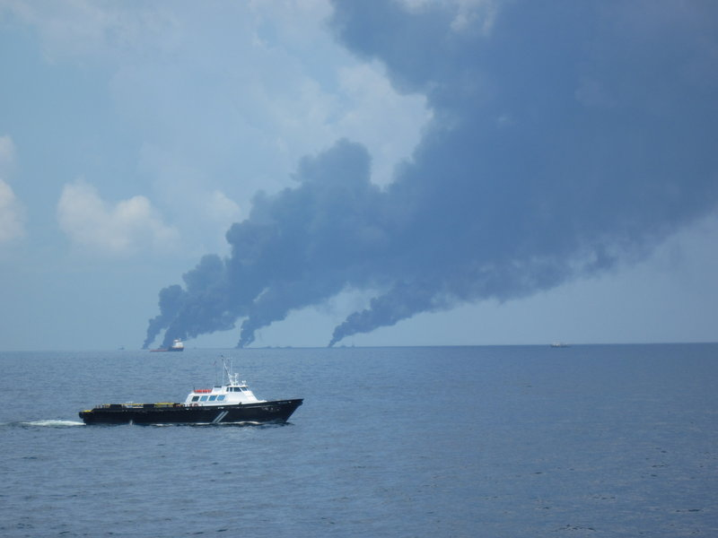 The Mr. Leroy, one of many boats that supply vessels cleaning up oil, nears the Maine Responder as smoke from controlled burns billows on the horizon. Supply boats carry food, water, equipment and passengers.