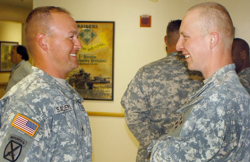 Cpl. Joseph Sanders, left, and Spc. Albert Godding talk at Fort Polk, La., before Godding received a Meritorious Service Medal in April for preventing Sanders' suicide in 2008.