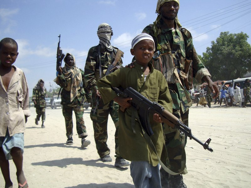 In this January file photo, a young Somali boy leads the hard-line Islamist Al Shabab fighters as they conduct military exercise in northern Mogadishu's Suqaholaha neighborhood.