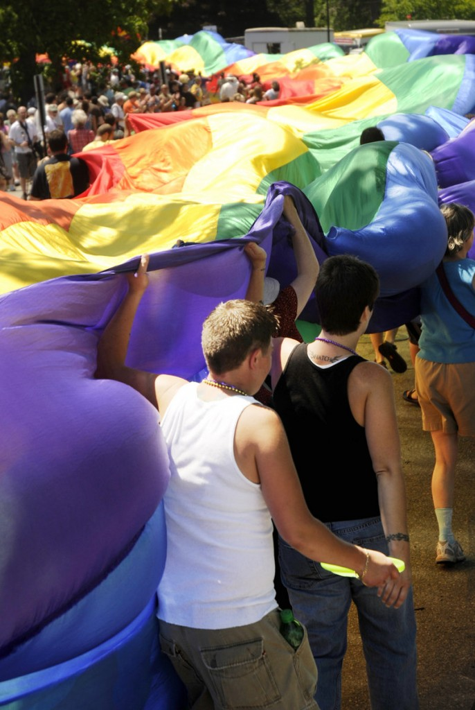 Participants carry a massive rainbow flag as they snake through Deering Oaks park in Portland. The parade began at Monument Square.
