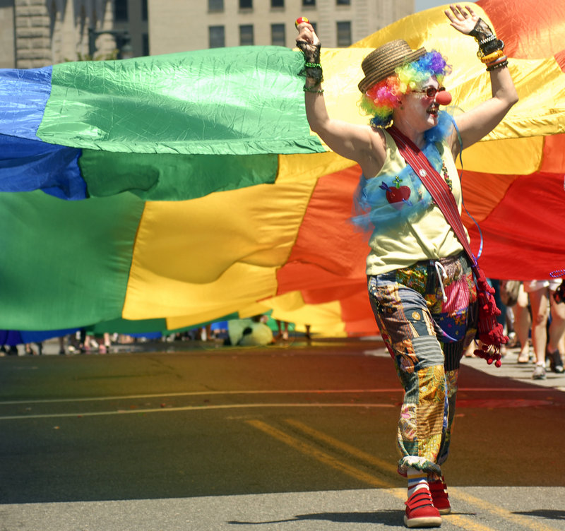 Lorrayne Carroll marches along Congress Street in front of the massive rainbow flag.
