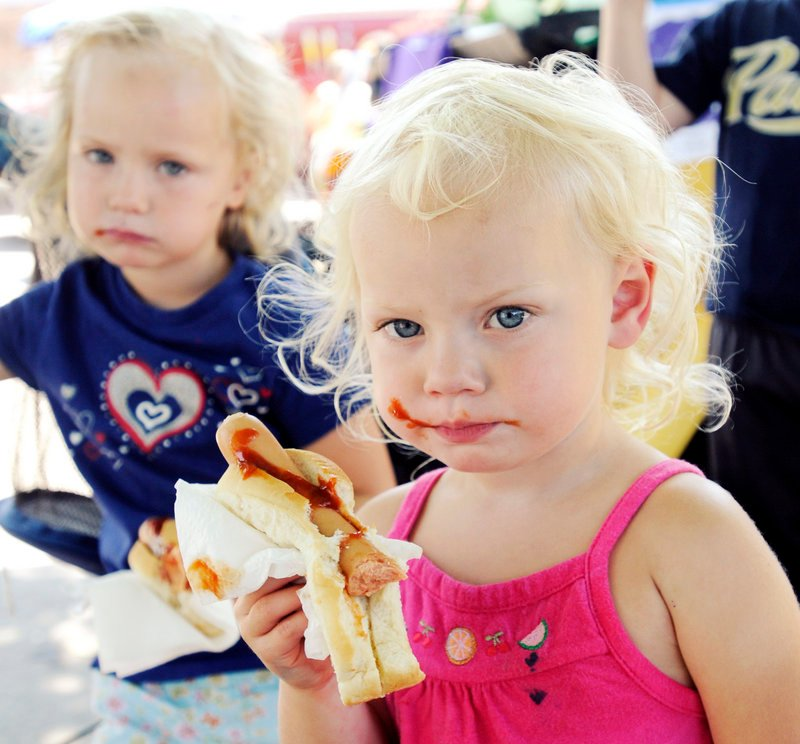 Avery Green, 2, eats a messy hot dog lunch with her sister, Bella, 4, at PeaksFest.