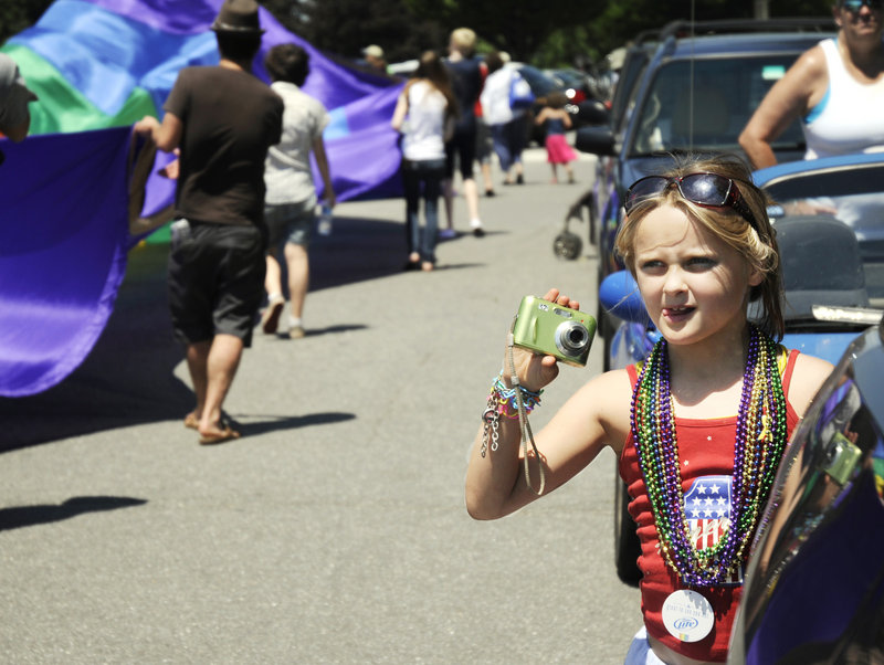 Rhyleigh Metcalf, 7, holds her camera steady as she snaps a photo of the parade.