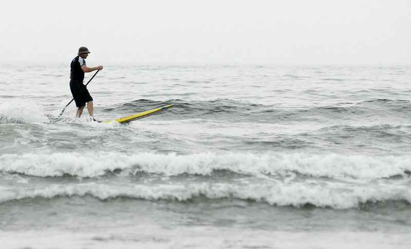 Mark Spaulding of Kennebunk catches a wave Sunday at Higgins Beach in Scarborough. The event was sponsored by the Northern New England chapter of the Surfrider Foundation, one of whose goals is to help modify beach access laws in Maine. The group worked with town officials and the Trust for Public Land to buy a family-owned parking lot near the beach.