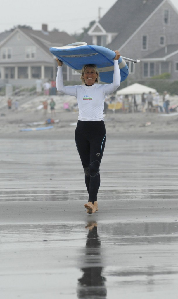 Nancy Boutet of Aquaholics surf shop in Kennebunk heads to the ocean