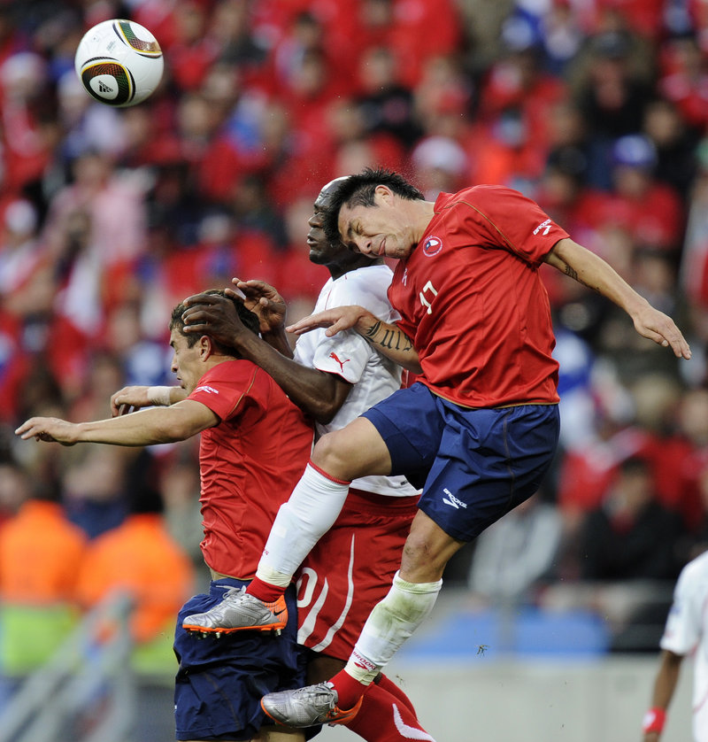 Chilean teammates Carlos Carmona, left, and Gary Medel, right, fight for the ball with Switzerland's Blaise Nkufo on Monday in Port Elizabeth, South Africa. Chile won, 1-0.