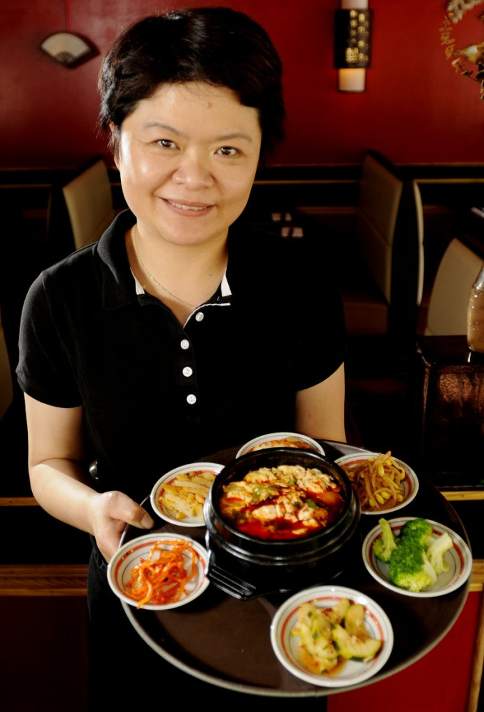 Soju's owner Catherine Burrill with a soft tofu chigae (spicy tofu stew) surrounded by house kimchees.