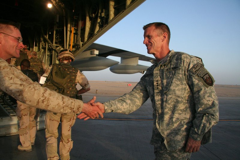 U.S. Gen. Stanley McChrystal, right, shakes hands with a Marine before boarding a military plane last year at Camp Leatherneck base in the southern province of Helmand, Afghanistan. McChrystal's job as the war's U.S. commander appeared in jeopardy Tuesday as an infuriated President Obama summoned him to Washington.
