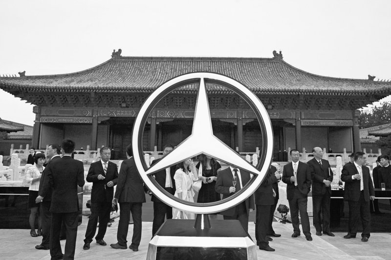 Guests stand next to a large Mercedes Benz logo at the launch of the automaker's S Class in Beijing last year.
