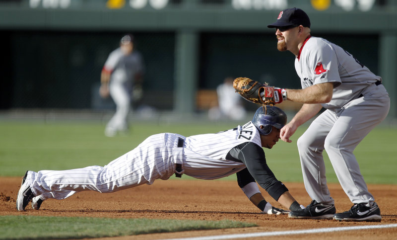 Carlos Gonzalez of the Colorado Rockies dives back to first base Tuesday night as Kevin Youkilis of the Boston Red Sox prepares for a pickoff throw. Colorado won, 2-1.