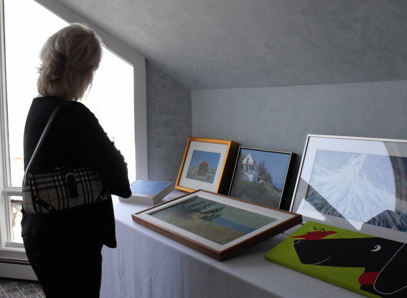 Gail Arnold, president of the Animal Welfare Society, looks over pieces of art donated for the AWS art auction, held May 23 in Kennebunk.
