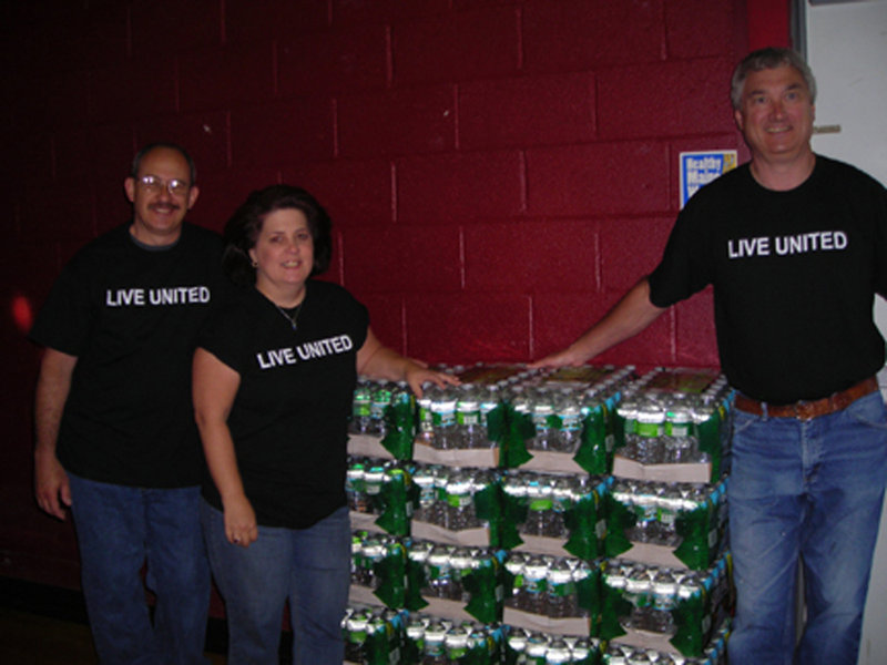 John Cote of Pratt & Whitney, left, Day of Caring Chair Lisa Randall of Kennebunk Savings, center, and volunteer Jeff Fowler provide water supplied by Poland Spring during the United Way of York County's Day of Caring on June 9.