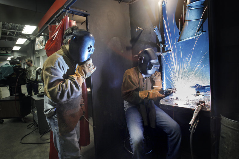 Joel Boehm, 14, welds a sculpture together as Griffin Klene, 17, watches on Wednesday. The two are taking part in the Mind Over Metal manufacturing skills camp at Southern Maine Community College this week.