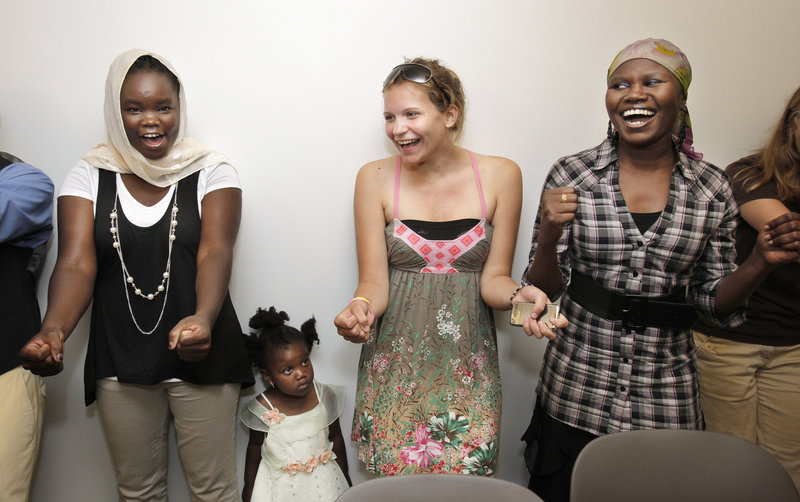 """Susan Zackaria, her daughter Hadil, 2, Ellie MacEwan and Sudanese graduate Marwa Abdalla participate in a """"celebration circle"""" chant at the end of a graduation ceremony at Portland Public Library on Wednesday for the Refugee Leaders Capacity Building program."""