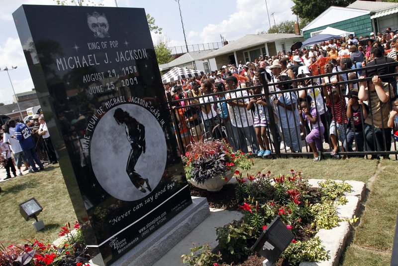 Michael Jackson fans gather around a monument that was unveiled Friday in the singer's hometown of Gary, Ind., on the first anniversary of the pop icon's death.