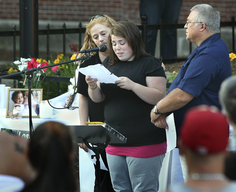 Allie Pertel, the half-sister of Megan Waterman, reads a prayer as Megan's mother Lorraine Ela and Pastor Mark Drinkwater look on at a candlelight vigil for the missing woman at Congress Square in Portland on Friday.