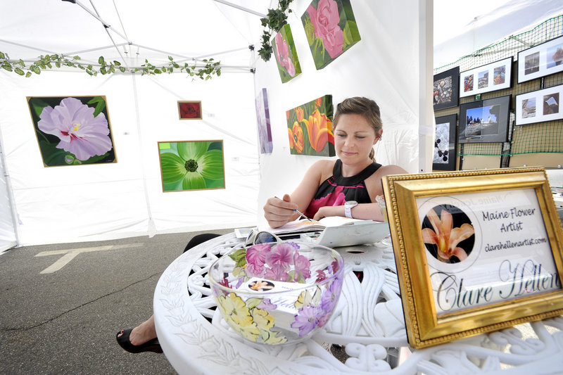 Portland artist Claire Hellen paints watercolor flowers as she displays oil paintings at the Saco Spirit Art Festival in Saco.