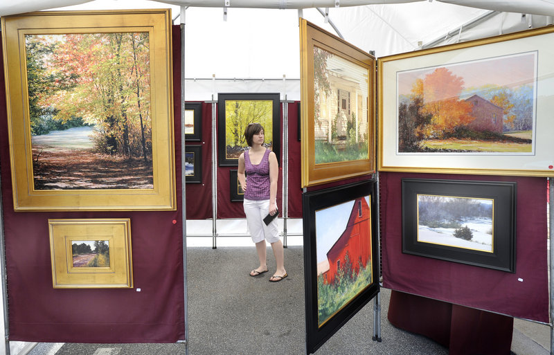 Angela Dupuis of Saco wanders through a display of paintings by Stephen Previte, an artist from Hollis, N.H.