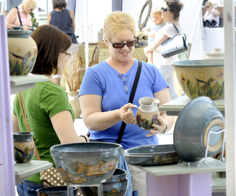Justine Bald and her mother, Darlene Lessart, of Biddeford check out pottery.