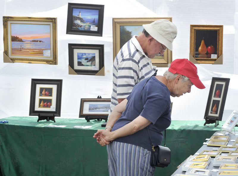Bob and Priscilla Kelley of Saco examine some of the smaller pieces of artwork at the Saco Spirit Art Festival.