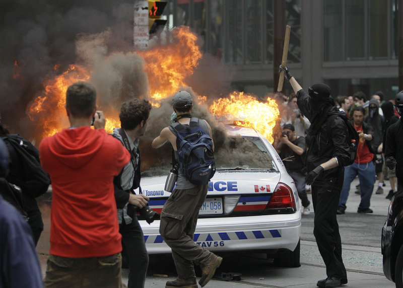Protesters surround a burning police cruiser during demonstrations in Toronto on Saturday, as the G-20 summit got under way. Some protesters also hurled bottles at police.