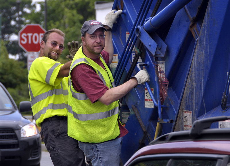 Staff Writer Ray Routhier, right, rides a garbage truck Thursday with Nick Albano, a Portland trash collector.