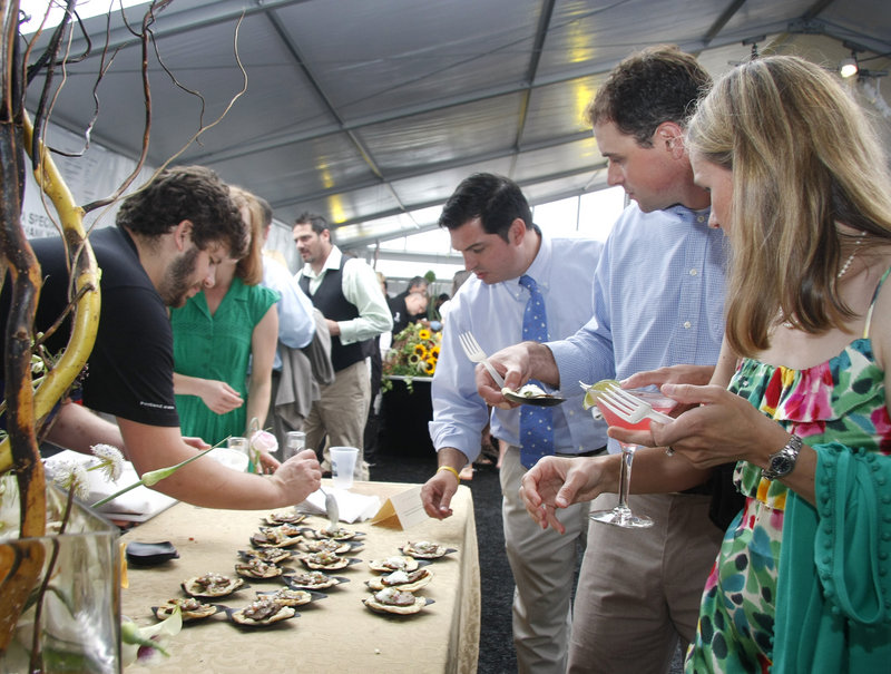 Erin and Kevin Morneault of Falmouth, right, and Mark Simmons of Concord, N.H., center, watch as chef Andrew Taylor of Hugo's in Portland serves Gedalis Farm goat taquitos at Taste of the Nation's Share Our Strength benefit Sunday at the Ocean Gateway Terminal in Portland.