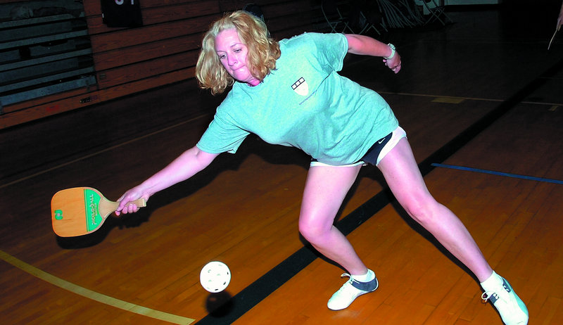 Kathy Welch returns a shot during a doubles match of pickleball at the Alfond Youth Center in Waterville. The game combines features of badminton, pingpong and tennis.