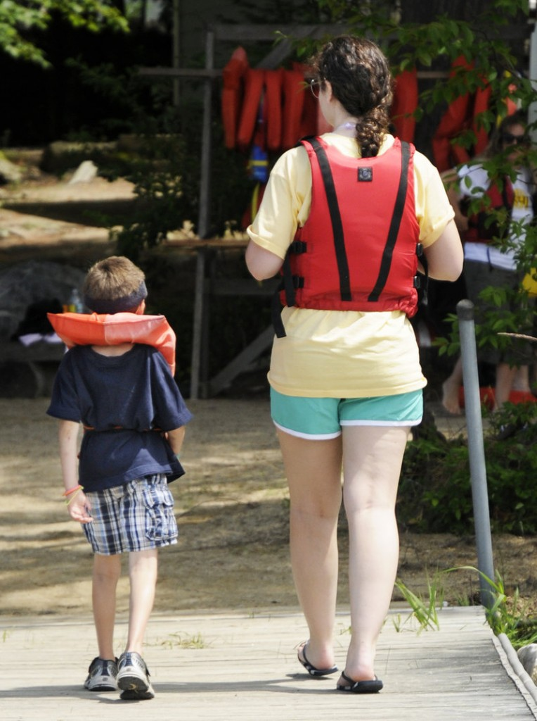 Wesley Young, 7, and volunteer Stephanie Reeves take a stroll after a paddle boat ride during Fanconi anemia week at Camp Sunshine on Sebago Lake.