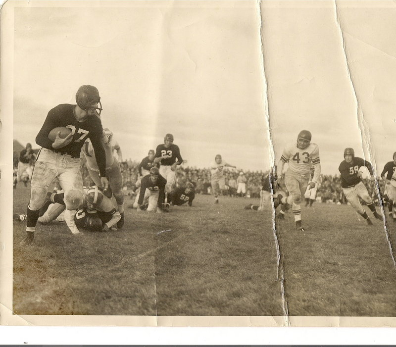 Arthur Bishop runs with the football during a game between Bowdoin and Colby colleges in 1951. He wore a guard to protect his broken nose.
