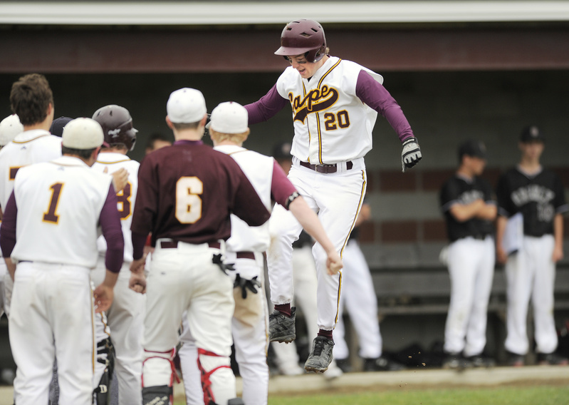 Will Pierce of Cape Elizabeth leaps on the plate and is greeted by teammates Saturday after a two-run homer in the third inning of a 4-3 victory over Greely in a Western Class B semifinal.