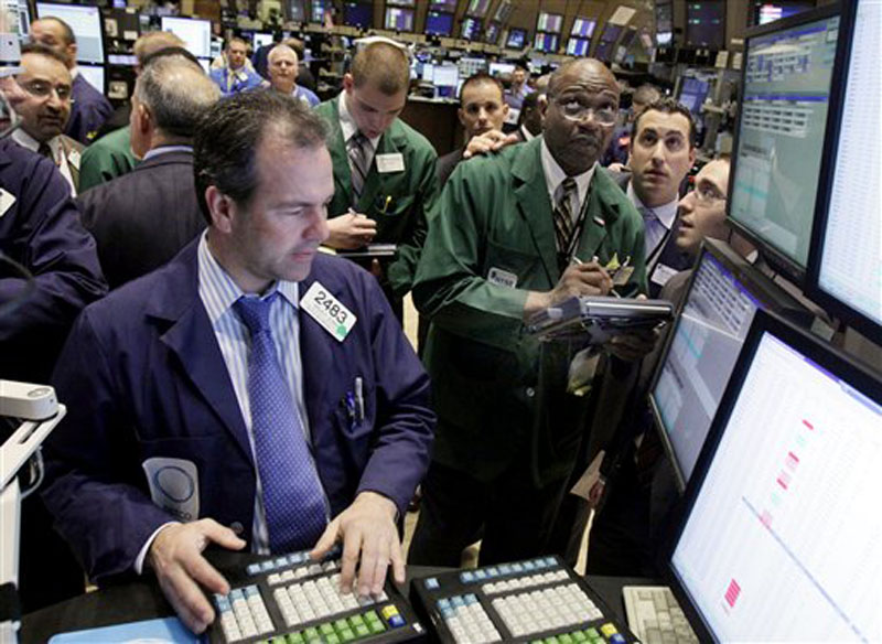 In this file photo, specialist Brian Quinn, left, works at his post on the floor of the New York Stock Exchange. Stock futures and interest rates tumbled today after fresh signs of a global economic slowdown spooked investors.