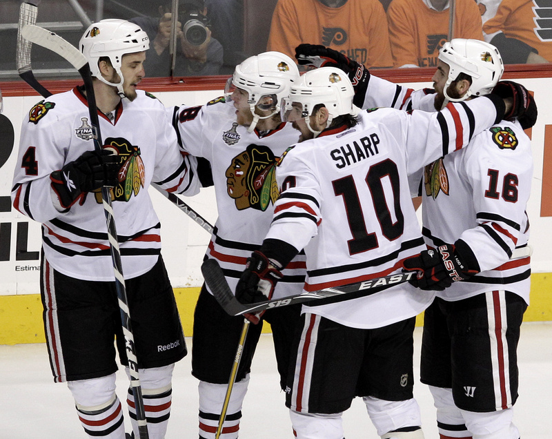 Andrew Ladd, right, celebrates with, from left, Niklas Hjalmarsson, Patrick Kane and Patrick Sharp after scoring for the Blackhawks in their Cup-clinching overtime win.